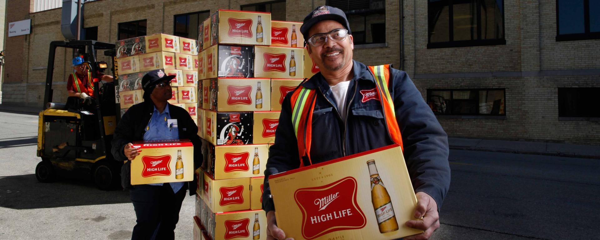 Employees holding Miller High life boxes