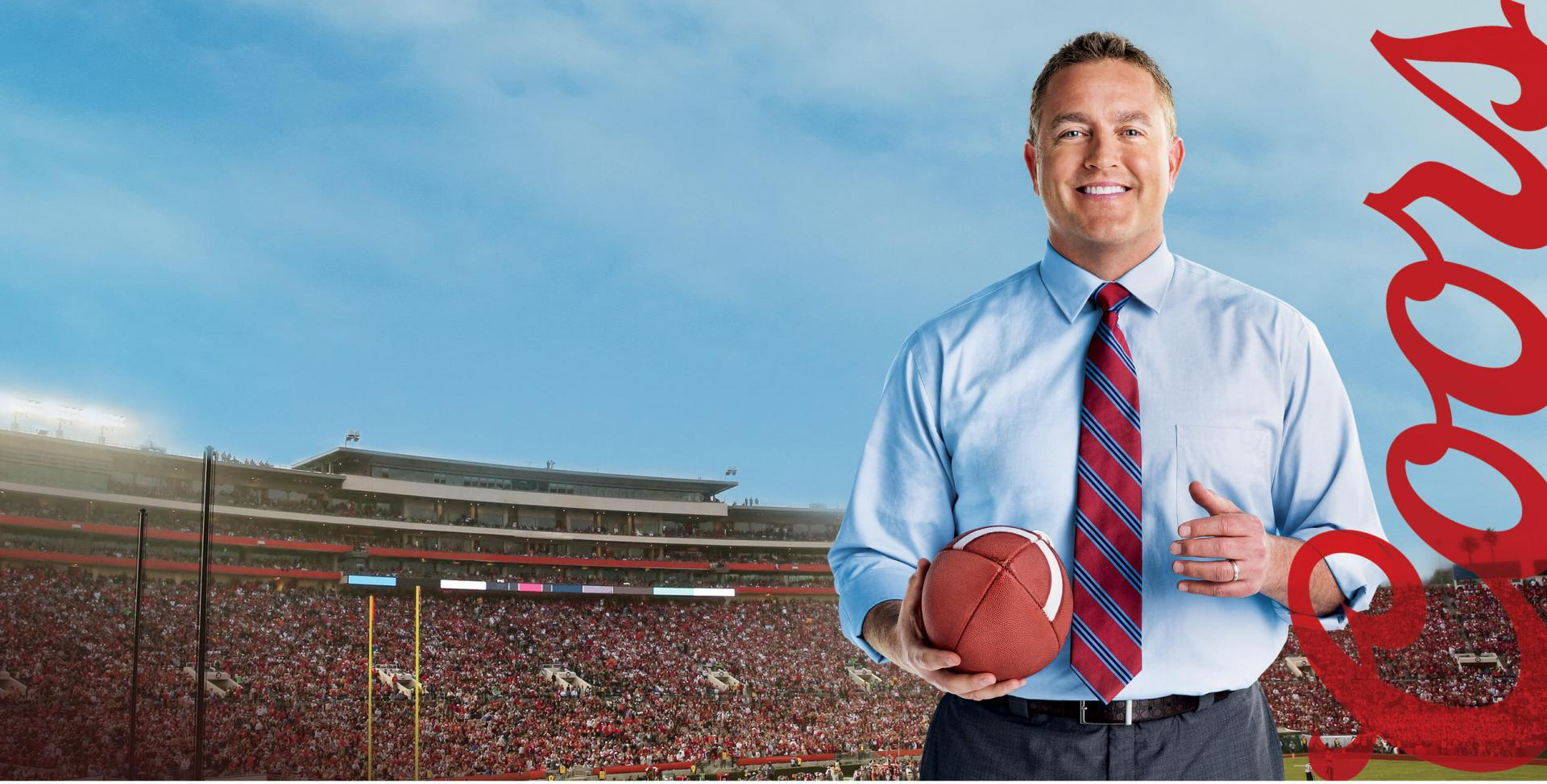 Man at stadium holding an american football ball