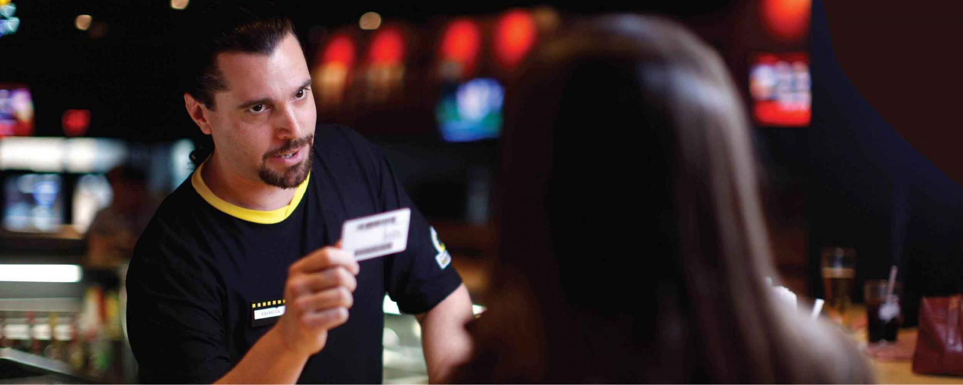 man at bar reviewing ID