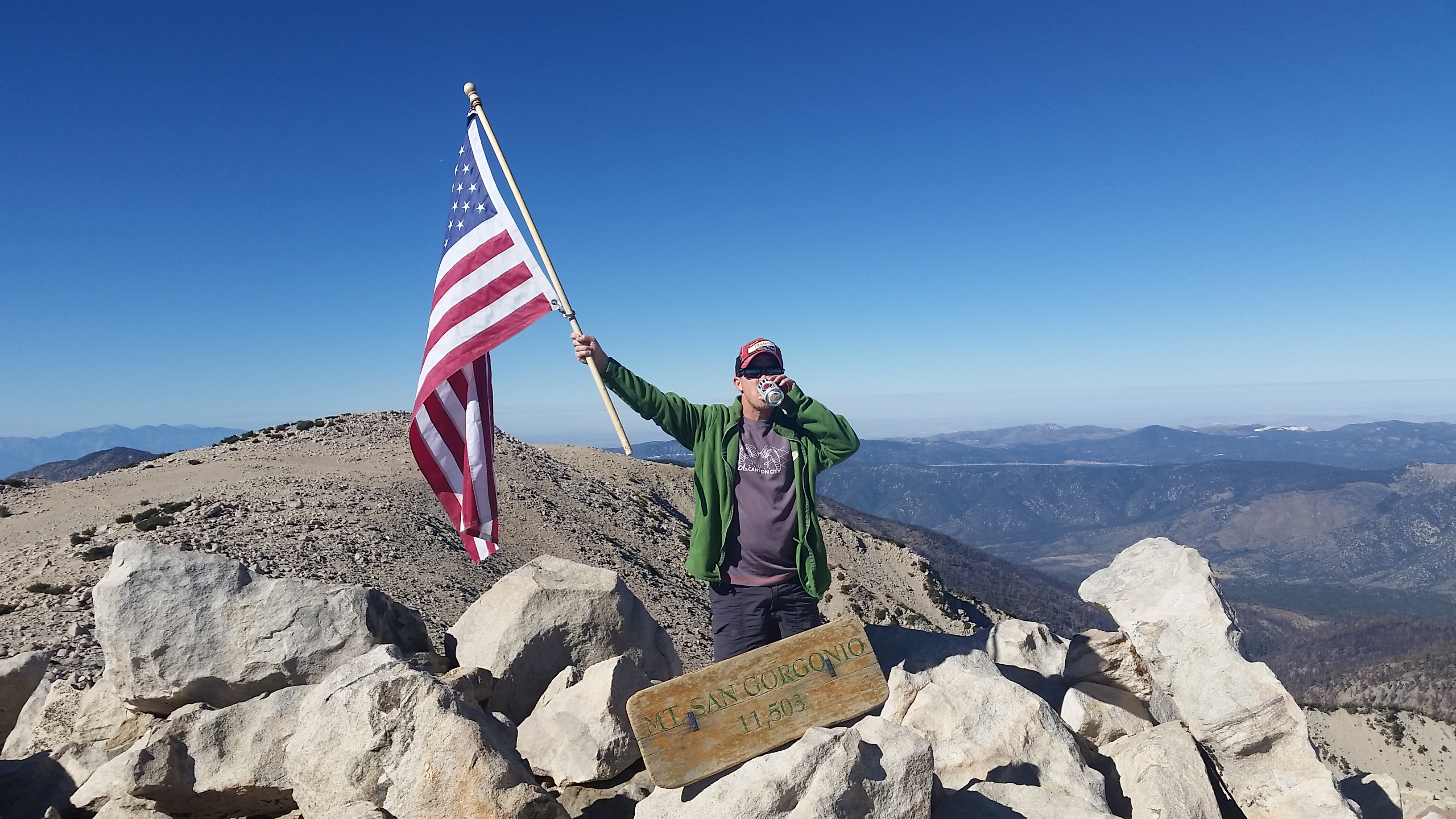 Image of Bryan Wells celebrating a successful climb to mountain top (with Miller Lite in hand)