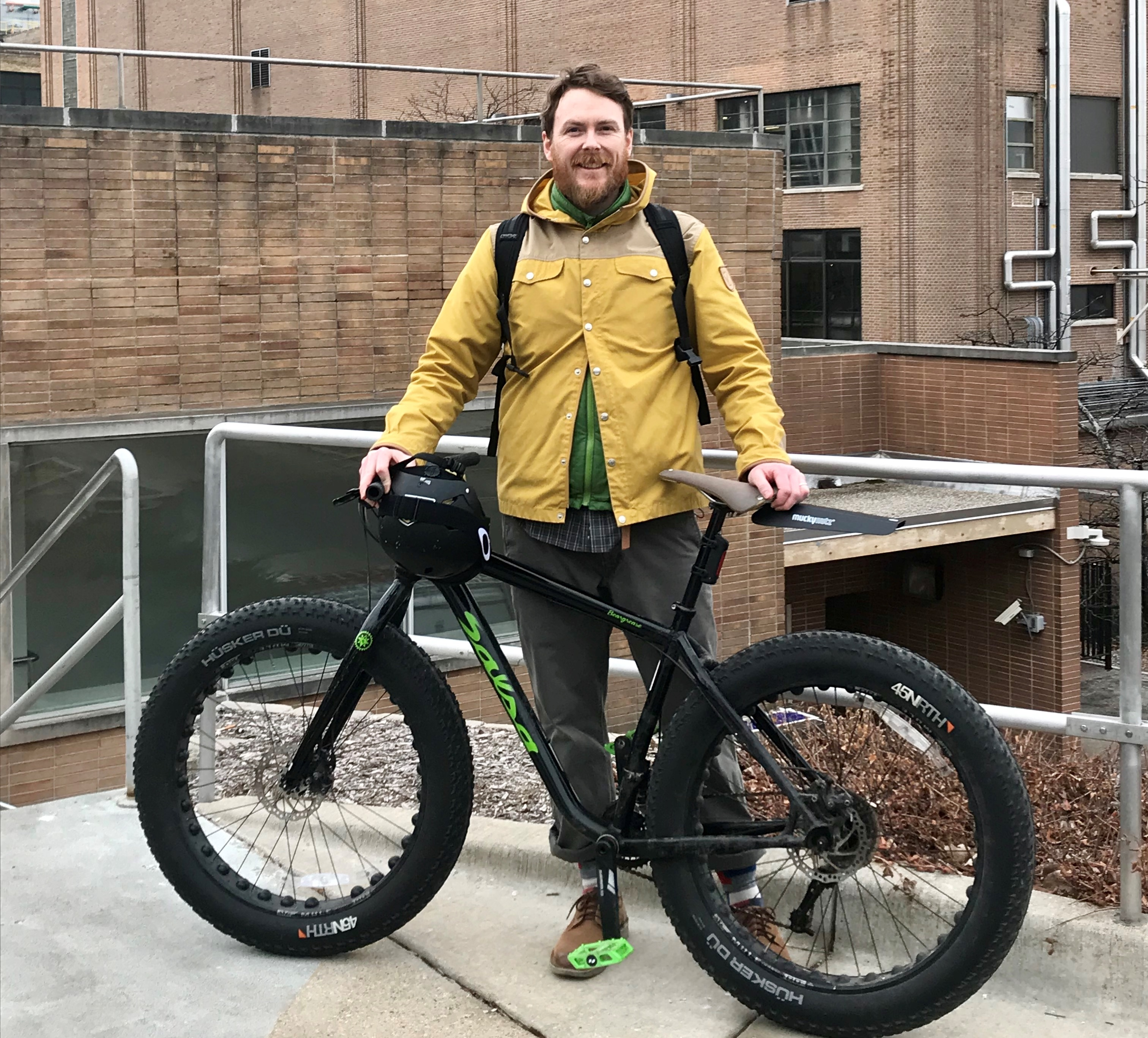 Josh R. standing in front of bike on Milwaukee campus