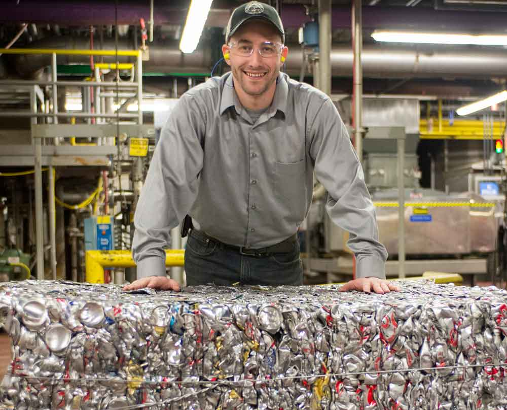 Man at factory with recycled beer cans
